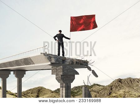Rear View Of Confident Businessman In Suit Holding Flag In Hand While Standing On Broken Bridge With