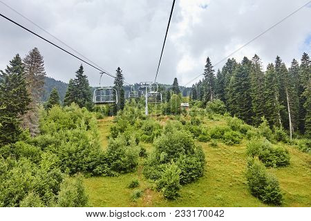 Emtpy Chairlift In Ski Resort. Mountains And Hills With In Summer With Green Trees And Grass