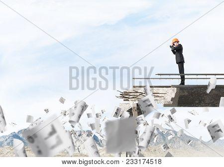 Young Engineer In Suit And Helmet Looking In Binoculars While Standing Among Flying Papers On Broken