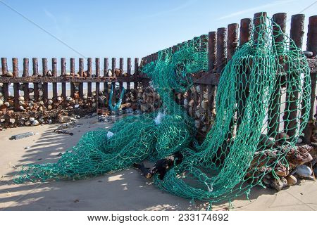 Sea Fishing Net Washed Up On The Beach. Ocean Pollution. Green Nylon Plastic Environmental Hazard An