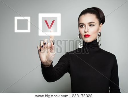 Attractive Woman Pointing Her Finger At Red Checkmark In Checkbox. Young Businesswoman Voting On Gra