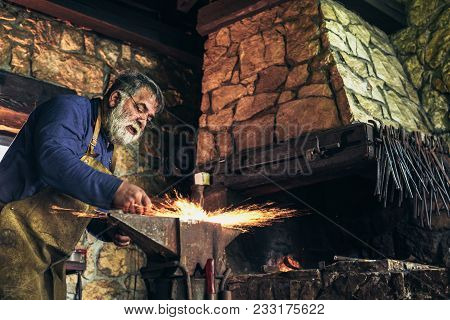 The blacksmith manually forging the molten metal on the anvil in smithy with spark fireworks poster