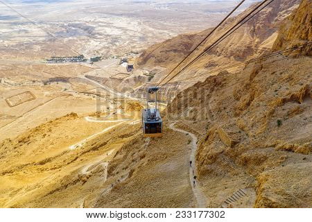 Masada, Israel - March 16, 2018: The Cliff And Fortress Of Masada, Cable Cars And Visitors Climbing