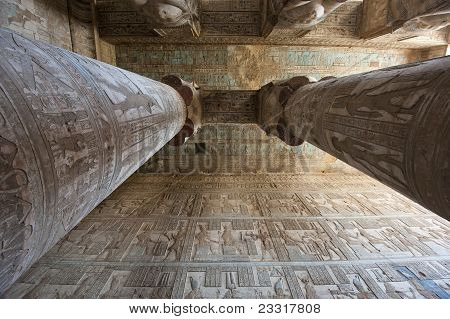 Columns inside an ancient egyptian temple covered in hieroglyphic carvings and paintings poster