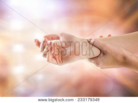 Digital composite of Hand restraining arm with sparkling light bokeh background