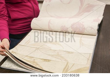 Female Hand, Choosing The Right Color From The Catalog Of Wall-papers In The Room Close-up