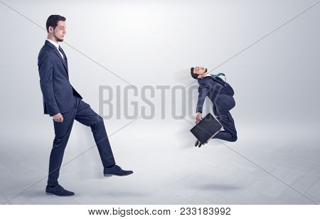 Small young man fired by his bos from his workplace with suitcase on his hand