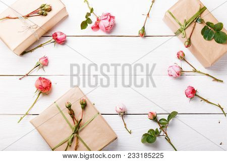 Gift And Roses On Wooden White Background. Workspace. Top View, Flat Lay