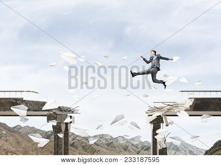 Businessman Jumping Over Gap In Bridge Among Flying Paper Planes As Symbol Of Overcoming Challenges.