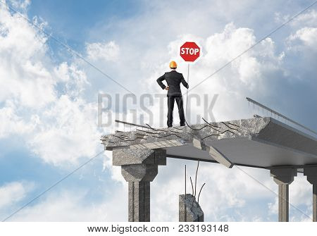Rear View Of Engineer In Helmet Holding Stop Sign While Standing On Broken Bridge With Skyscape On B