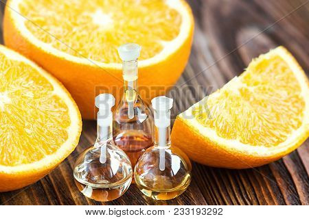 Essential Aroma Oil In Glass Bottle With Fresh, Juicy, Ripe, Orange Fruit On Wooden Background. Beau
