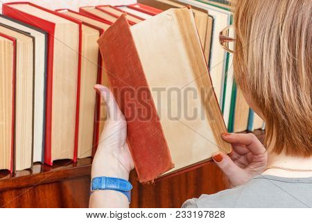 Woman With Glasses Is Taking An Old Book From A Bookshelf. Many Hardback Books On Wooden Shelf. Libr
