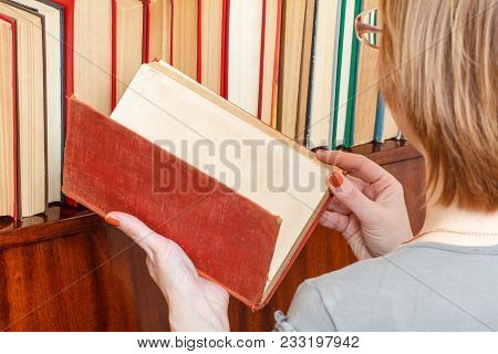 Woman With Glasses Is Holding An Old Book Nex To A Bookshelf. Many Hardback Books On Wooden Shelf. L