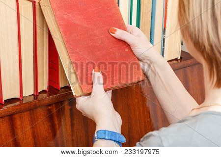 Woman Is Holding An Old Book Nex To A Bookshelf. Many Hardback Books On Wooden Shelf. Library Concep