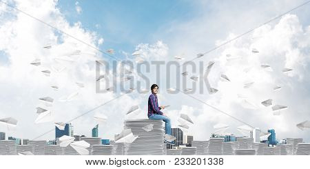 Young Man In Casual Clothing Sitting Among Flying Paper Planes With Cloudly Skyscape On Background.