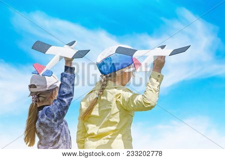 Happy Two Girls Kid Playing With Toy Airplane Against Blue Summer Sky Background. Concept - Inoculat