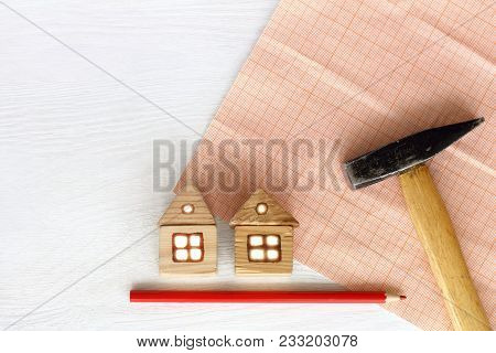 Two Wooden Home, Hammer, Red Pencil On Background Of Millimeter Paper On The Table / Repair Or Resto