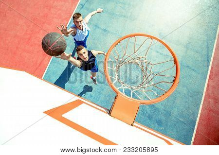 High Angle View Of Basketball Player Dunking Basketball In Hoop.