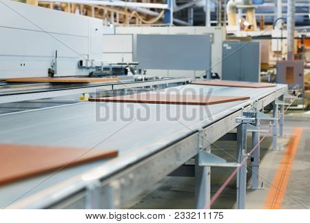 production, manufacture and woodworking industry concept - chipboards processing on conveyer at furniture factory workshop