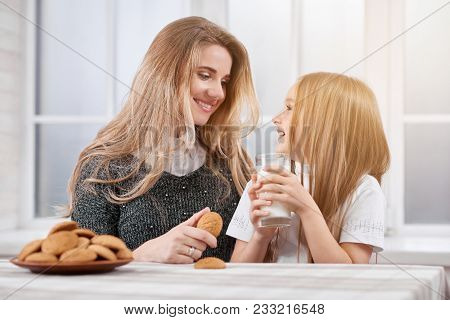 Photo Of Two Laughing Sisters-younger And Oder. Both Girls Have Blonde Straight Hair. They Are Eatin