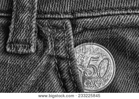 Euro Coin With A Denomination Of Fifty Euro Cents In The Pocket Of Old Denim Jeans, Monochrome Shot.