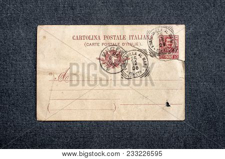 Old Postcard On Dark Background. Vintage Empty Italian Postcard With Postage Stamps
