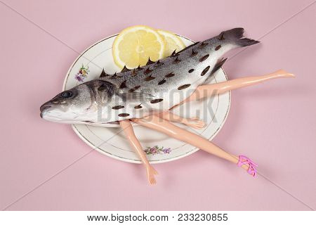 A Bass Fish With Arms And Legs Of A Doll Inside On A Flower Plate. Cannibalism And Anthropomorphism