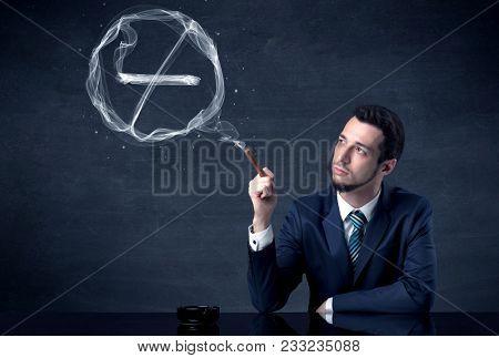 Businessman smoking cigarette and the smoke forms a no smoking sign.