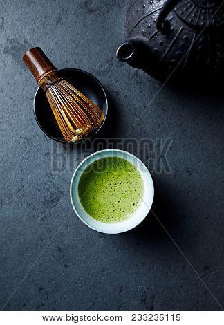 Cup of Matcha Green Tea on dark stone background; tea whisk, cast ron tea pot, japanese ceramic