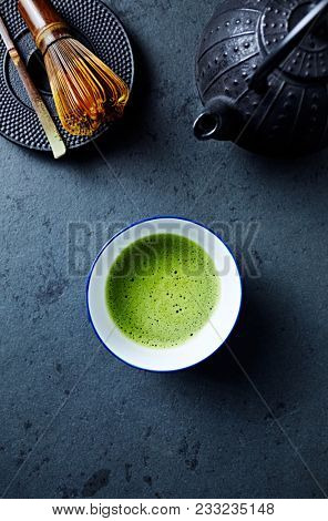 Cup of Matcha Green Tea on dark stone background; tea whisk, cast ron tea pot, japanese ceramic poster