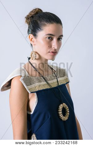 Young Latin Model Wearing A Blue Shirt And A Rounded Recycled Paper Necklace And Earrings