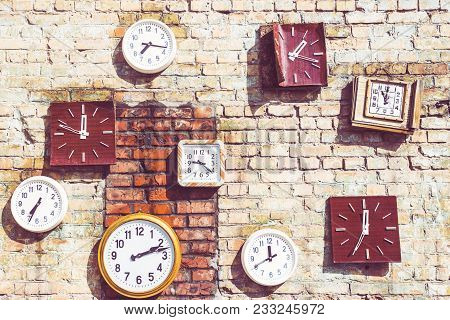 Old Retro Vintage Wall Clock On A Brick Loft Wall From The Outside Of The Building. The Course Of Ti