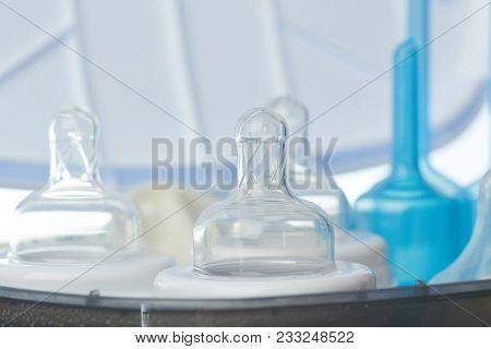 Close-up Of Clean Plastic Bottle Nipple In Sterilizer Machine