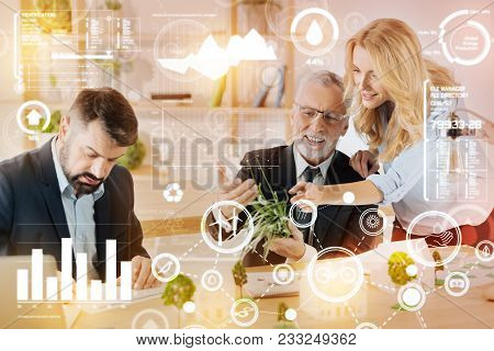 Look Here. Enthusiastic Cheerful Man Sitting At The Table And Smiling While Showing A Bunch Of Grass