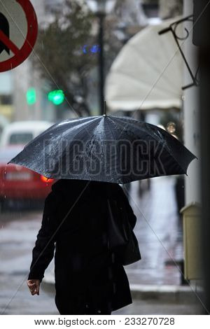 Woman In Rain Walking With An Umbrella.