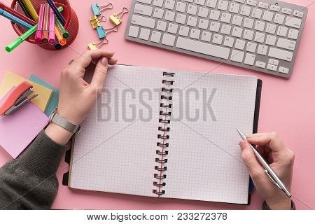 Woman's Hands Writing In Spiral Notepad