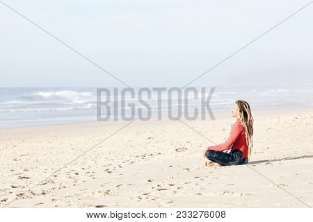 Young adult surfer with dreadlocks wearing wetsuit sitting cross-legged on beach near spot and meditating before summer evening surfing session - yoga and surfing concept. Baleal, Peniche, Portugal