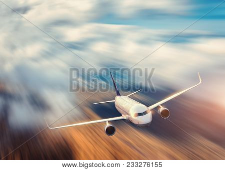 Modern Airplane With Motion Blur Effect Is Flying Over Low Clouds At Sunset. Passenger Airplane, Blu