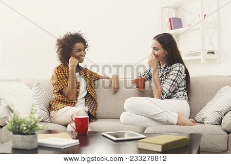 Two Happy Young Female Friends With Coffee Cups Conversing In Living Room At Home, Chatting About Th