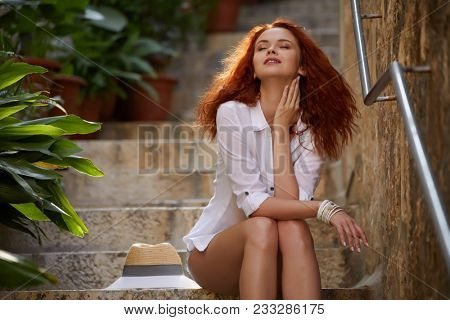 Portrait of happy smiling woman standing on the square on sunny summer or spring day outside, cute smiling woman looking at you, attractive young girl enjoying summer