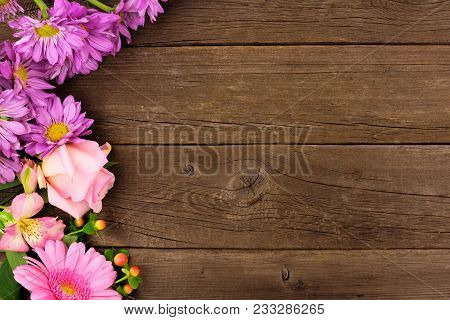 Side Border Of Pink And Purple Flowers With Rose, Daisies And Lilies Against A Rustic Wood Backgroun