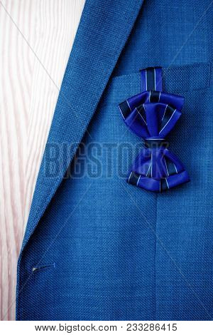Dark Blue Bow Tie With Black Stripes Hanging Out Of Blue Suit Jacket On Light Brown Wood Background.