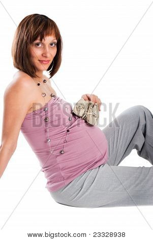 The Pregnant Woman With Bootees On A White Background