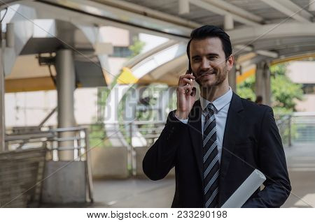 Smart Caucasian Business Man Wearing Modern Black Suit Making Phone Call With Mobile Smart Phone In