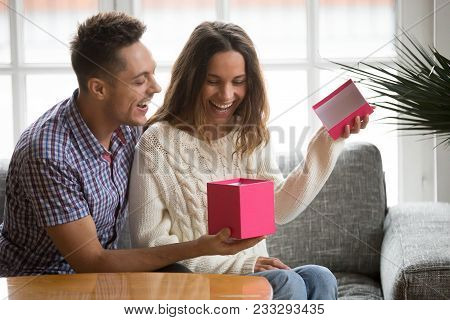 Excited young woman opening gift box receiving good unexpected present from husband at home, loving generous boyfriend making romantic surprise to attractive girlfriend on Valentines day occasion poster