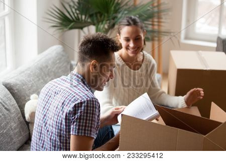 Young Man Holding Book Helping Wife To Pack Cardboard Boxes On Moving Day, Smiling Young Couple Unpa