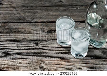 Two Shot Glasses With Cold Vodka Or Gin On Wooden Table, Copyspace Top View