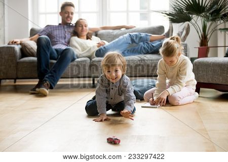 Cute Kids Playing While Parents Relaxing Sofa At Home Together, Smiling Active Boy Entertaining With