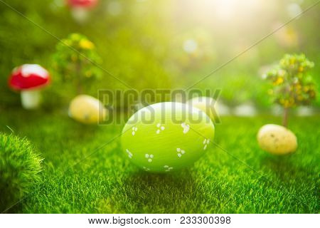 Happy Easter Concept. Colorful Easter Eggs And One Big Green Easter Egg On Spring Green Grass. Fairy