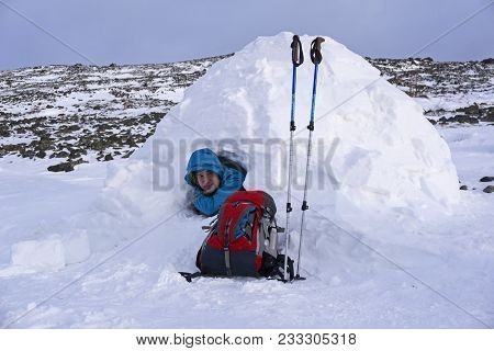 Traveler Looks Out Of A Snowy House Igloo Against A Background Of A Winter Mountain Landscape
